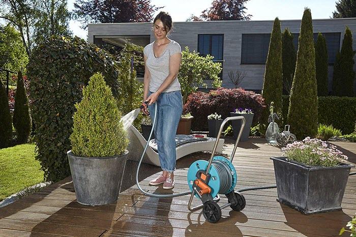 Une femme jardine avec ton enrouleur de tuyau d'arrosage équipé